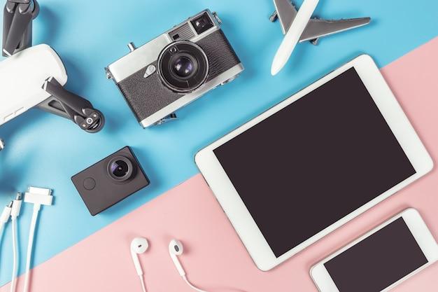 Gadgets de viagem flatlay em fundo azul e rosa para o conceito de viagens
