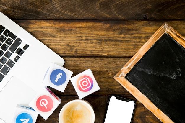 Gadgets eletrônicos, ardósia e café com ícones de mídia social e móvel