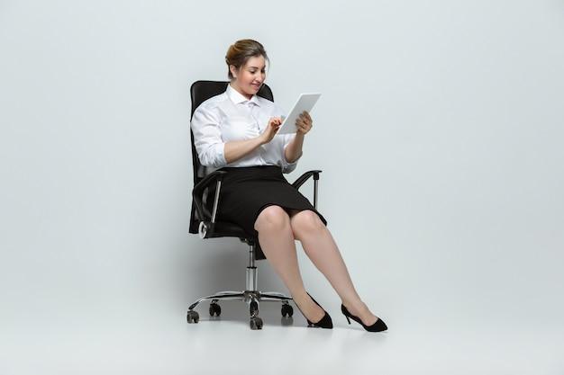 Gadgets. jovem mulher em trajes de escritório. personagem feminina bodypositive, feminismo, amar a si mesma, conceito de beleza. além disso, empresária de tamanho na parede cinza. chefe, lindo. inclusão, diversidade.