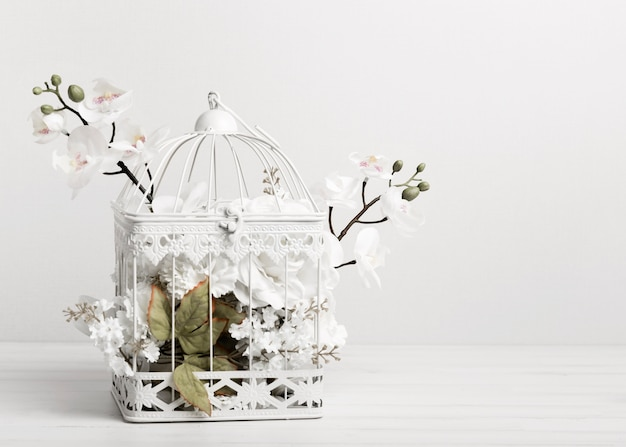 Gaiola de pássaro branca cheia de flores