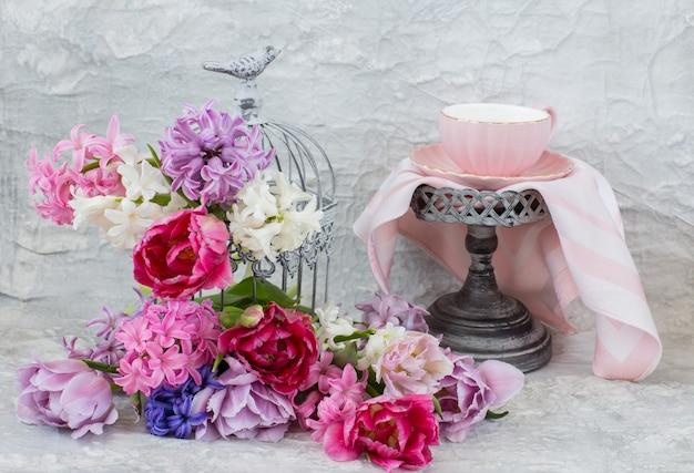 Gaiola decorativa e flores nele: jacintos e tulipas e uma xícara de chá