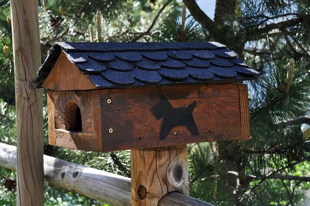 Gaiola para pássaros em forma de casinha de cachorro em uma cerca de madeira