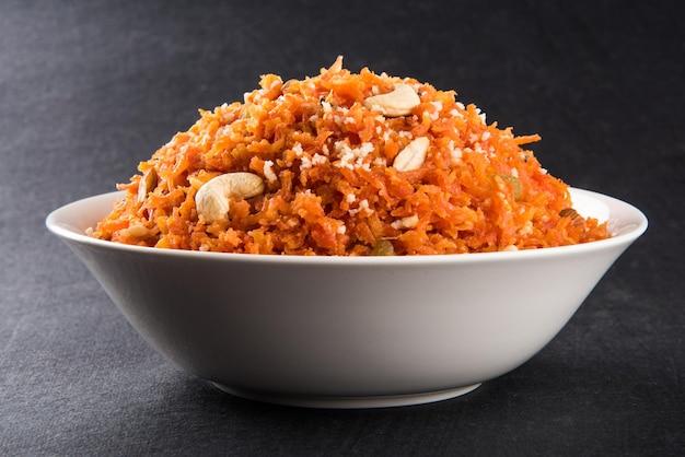 Gajar halwa é um pudim de sobremesa doce à base de cenoura da índia. guarnecido com castanhas de caju, amêndoas e servido em uma tigela sobre um fundo colorido de madeira