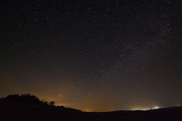 Galáxia, a via láctea no céu noturno com estrelas. espaço acima da superfície da terra. exposição longa.