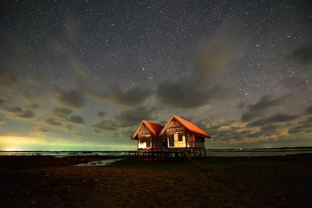 Galáxia da via láctea e estrela sobre duas casas à noite, talenoi tailândia