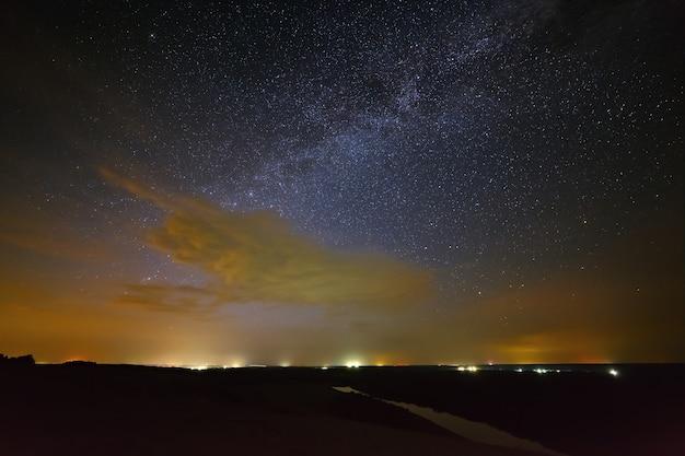 Galáxia via láctea com nuvens no céu noturno contra o fundo do rio
