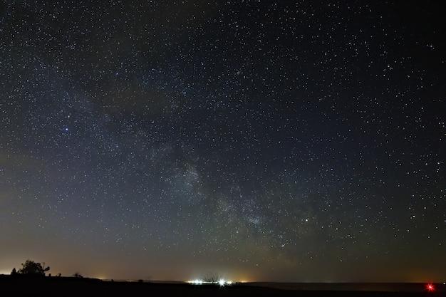 Galáxia via láctea com nuvens no céu noturno
