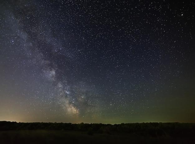 Galáxia, via láctea, no céu noturno, num contexto de floresta densa.