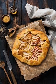 Galette de maçã, torta, bolo com mel e açúcar de cana em uma superfície de madeira. copie o espaço. vista do topo.