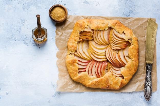 Galette de maçã, torta, bolo com mel e açúcar de cana na superfície de concreto leve. copie o espaço. vista do topo.