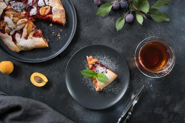 Galette de torta saborosa queda com ameixa e damasco na mesa preta.