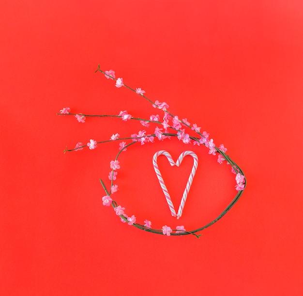 Galho com flores em forma de círculo e bastões de doces em forma de coração