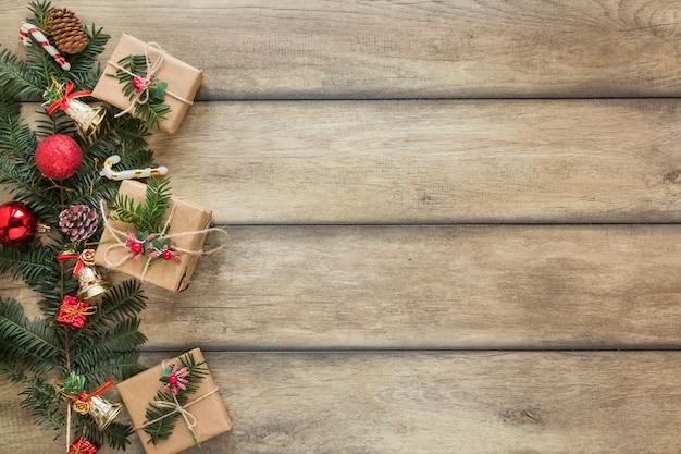 Galho de abeto decorado brinquedos de natal perto de caixas de presentes