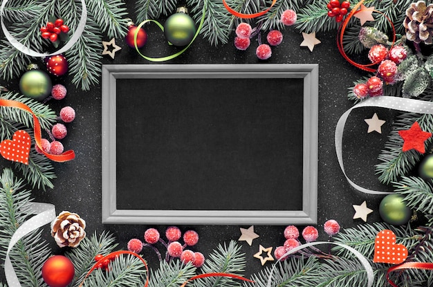 Galho de abeto decorado com enfeites, bagas e estrelas, quadro-negro, espaço de texto