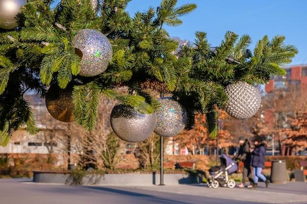 Galho de árvore de natal artificial com bolas de natal brancas na rua da cidade ao ar livre em dia ensolarado de inverno. família turva com criança caminhando.