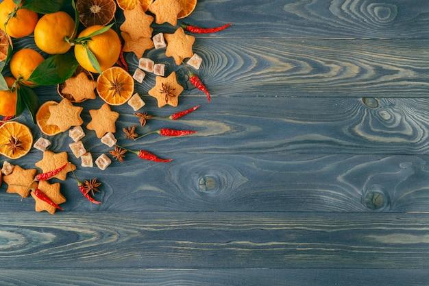 Galho de árvore de natal, biscoitos de natal e laranja seca no antigo fundo de madeira azul. pão caseiro cozido fresco.