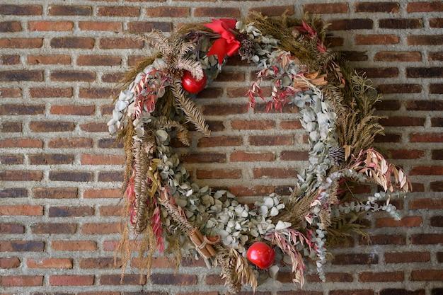 Galho de árvore de natal circulando bagas de azevinho na parede de tijolos galho de árvore de natal circulando bagas de azevinho na parede de tijolos