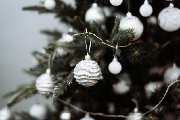 Galho de árvore de natal decorado com bolas de prata e festão branca.