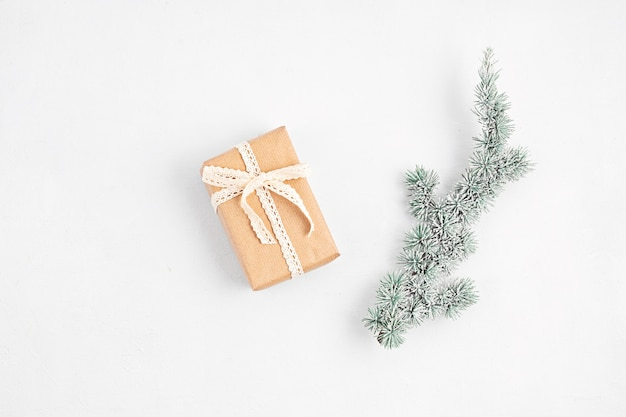 Galho de árvore de natal e caixa de presente embrulhados em papel artesanal orgânico, planta plana, vista de cima