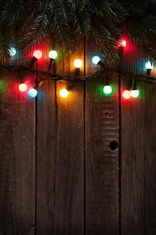 Galho de árvore de natal e luzes coloridas em fundo de madeira. ver com espaço de cópia