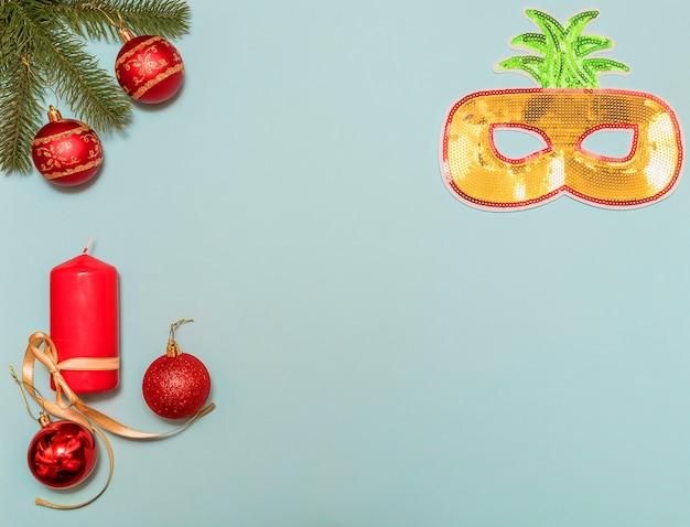 Galho de árvore de natal em suas bolas. máscara de ano novo em forma de ananás. vela vermelha e bolas vermelhas de natal. fundo azul.