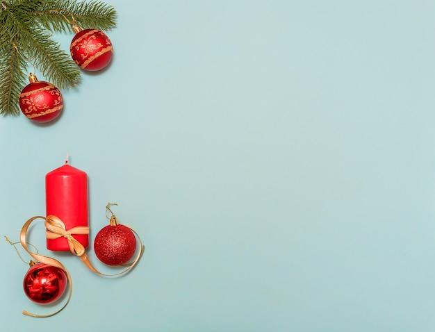 Galho de árvore de natal em suas bolas. vela vermelha e bolas vermelhas de natal. sobre um fundo azul. para design.