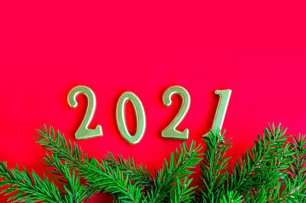 Galho de árvore de natal verde, vermelho sólido e número dourado 2021.