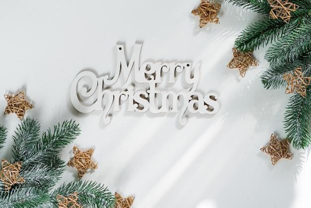 Galho de árvore do abeto com estrelas de madeira ouro e letras feliz natal em papel branco, vista superior copyspace