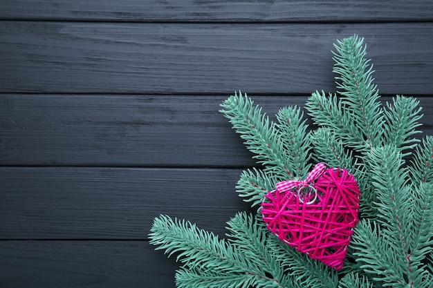 Galho de árvore do abeto com um coração rosa em um fundo preto.