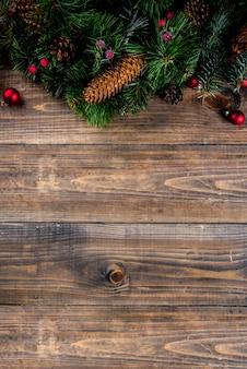 Galho de árvore do abeto de natal com pinhas e decorações na mesa de madeira. vista superior, copyspace.