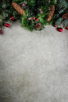 Galho de árvore do abeto de natal com pinhas e decorações na mesa de pedra cinza. vista superior, copyspace