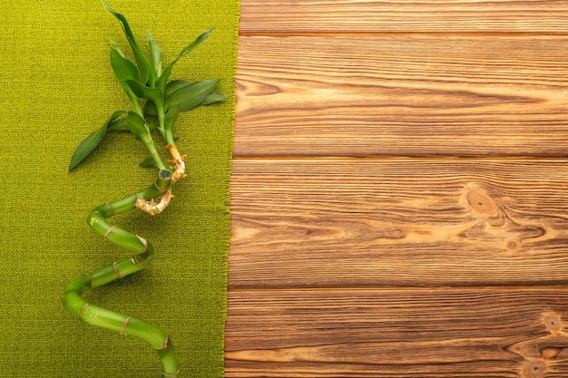 Galho de bambu com toalha verde sobre fundo de madeira