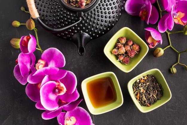 Galho de flor de orquídea rosa fresca e chá de ervas em fundo preto