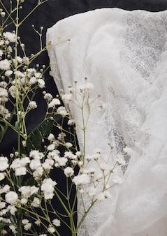 Galho de flor fresca perto de têxteis brancos