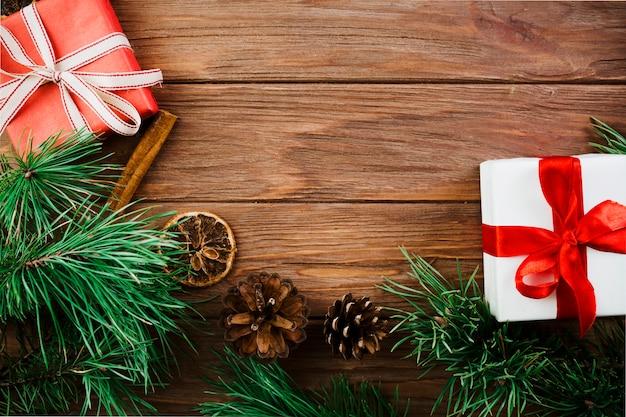 Galho de natal e caixas de presentes na mesa de madeira