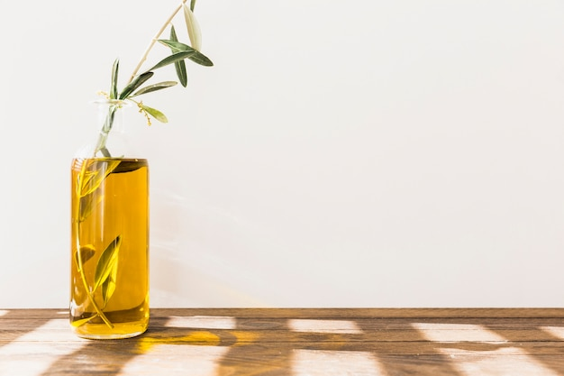 Galho de oliveira dentro da garrafa de óleo na mesa de madeira contra a parede