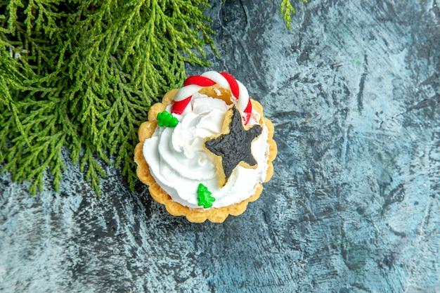 Galho de pinheiro de tortas de natal na mesa cinza