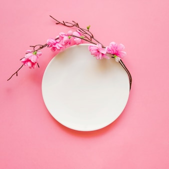 Galho em flor perto do prato