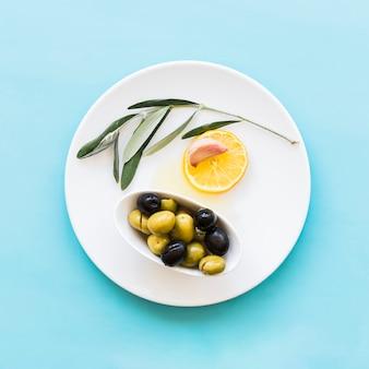 Galho, fatia de limão, dente de alho e tigela de azeitonas na placa sobre o fundo azul