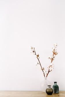 Galhos de algodão e vaso elegante de beleza em fundo branco
