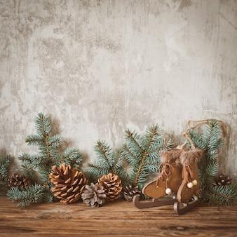Galhos de árvore de natal com cones em uma placa de madeira escura contra um muro de concreto cinza.