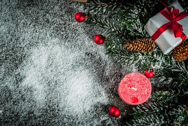 Galhos de árvore de natal com efeito neve com fita vermelha festiva, pinhas, caixas de presente e velas, em fundo azul escuro