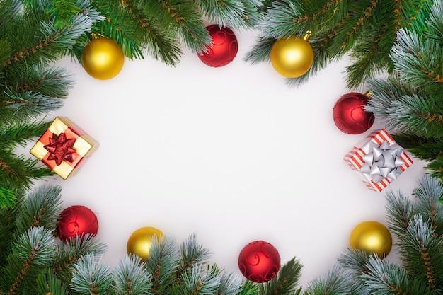 Galhos de árvore de natal em fundo branco com bolas de ouro e vermelho de natal