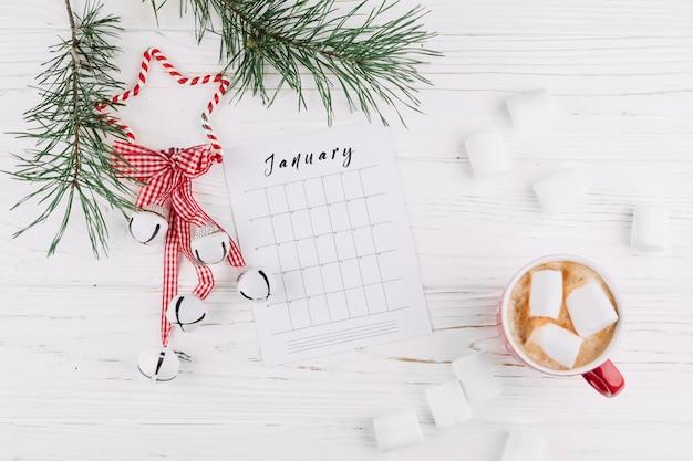 Galhos de árvore do abeto com calendário e jingle bells