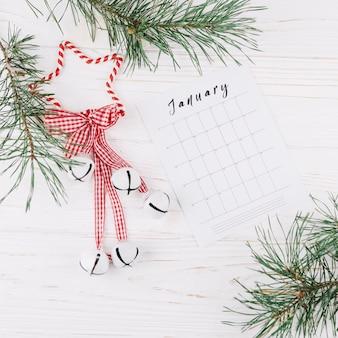 Galhos de árvore do abeto com calendário na mesa