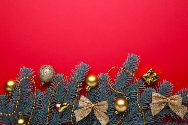 Galhos de árvore do abeto com decoração de natal em um fundo vermelho