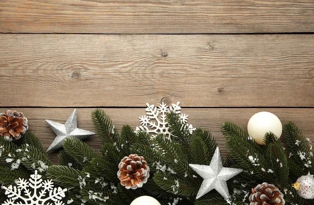 Galhos de árvore do abeto com decoração de natal prata sobre um fundo cinza