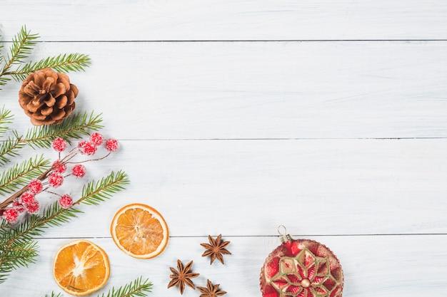 Galhos de árvore do abeto com laranja seca, estrelas de anis, bola de natal e cone em fundo branco de madeira.