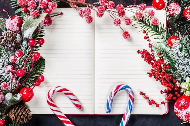 Galhos de árvore do abeto de natal, decorações, bastões de doces, frutas vermelhas congeladas, quadro de cone no notebook