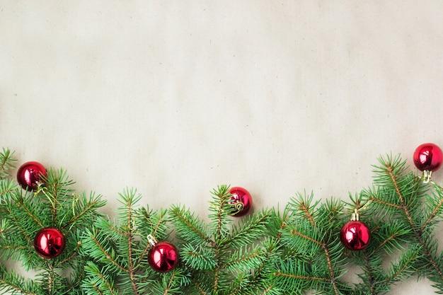 Galhos de árvore do abeto decorados com bolas vermelhas de natal como borda em um quadro de fundo rústico de férias com espaço de cópia